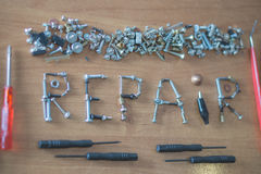 A word repair made of a lot of screws. Framed with screwdrivers and pincers on a desk Royalty Free Stock Images