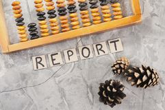 Word REPORT laid out of handwritten letters on cardboard squares near old wooden abacus and three cones. On gray cracked concrete stock image