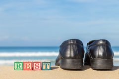 Word REST in colorful alphabet blocks and black shoe on tropical Royalty Free Stock Photo