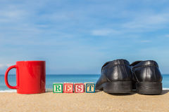 Word REST in colorful alphabet blocks and coffee cup on tropical Royalty Free Stock Images
