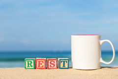 Word REST in colorful alphabet blocks and coffee cup on tropical Stock Photos