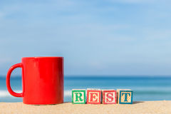 Word REST in colorful alphabet blocks and coffee cup on tropical Royalty Free Stock Image