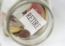 Savings. The word retire is shown in a mason jar with Canadian coins and a fifty dollar bill Stock Image
