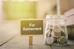 Word RETIREMENT on wooden signage and coin in jar .fade color effect wooden background with light effect. Concept image,word RETIREMENT on wooden signage and Stock Image