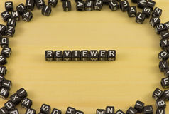 The word Reviewer. On wood background stock image