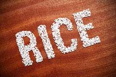 The word rice on a wooden surface. Royalty Free Stock Photography