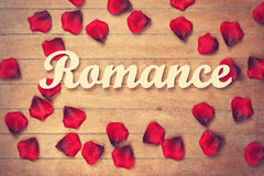 Word Romance and petals on wooden table. Royalty Free Stock Photos