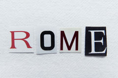 Word rome cut from newspaper on handmade paper Stock Photos