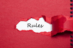 The word rules appearing behind torn paper. The word rules behind torn paper stock photos
