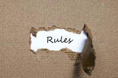 The word rules appearing behind torn paper. The word rules behind torn paper stock image