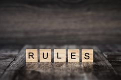 The word rules made of bright wood cubes with black letters on a. Dark wooden background royalty free stock images