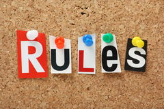 The word Rules. N cut out magazine letters pinned to a cork notice board Stock Image