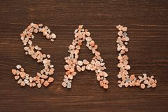 Word Sal written in pink Hymalayan salt crystals. On wooden background Royalty Free Stock Image