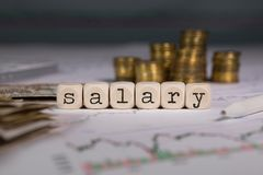 Word SALARY composed of wooden letter. Stacks of coins in the background. Closeup stock image
