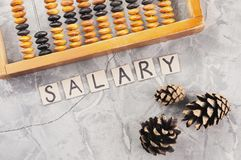 Word SALARY laid out of handwritten letters on cardboard squares near old wooden abacus and three cones. On gray cracked concrete stock images
