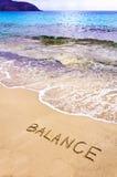Word SALDO op strandzand wordt geschreven, met overzeese golven op achtergrond die stock foto's