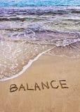 Word SALDO op zand, met overzeese golven op achtergrond wordt geschreven die Stock Fotografie