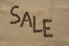 The word SALE from coffee beans on linea material Royalty Free Stock Image