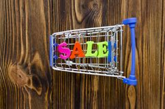 Word `sale` and empty shopping cart on wooden background.  Stock Photo