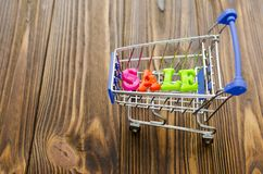 Word `sale` and empty shopping cart on wooden background. Word `sale` and empty shopping cart on wooden background Stock Photos