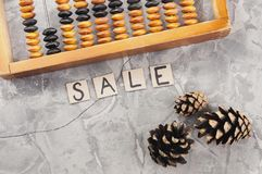 Word SALE laid out of handwritten letters on cardboard squares near old wooden abacus and three cones. On gray cracked concrete royalty free stock photography