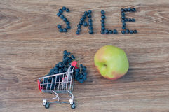 Word sale made of blue grapes and apple on table Stock Images