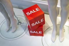 The word sale in shop window of clothing store. Next to mannequin legs Stock Image