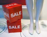 The word sale in shop window of clothing store. Next to mannequin legs Royalty Free Stock Photos