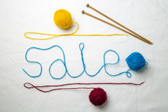 Word sale written multicolored yarn threads coiled into balls on a white background. Near wooden spokes lie Royalty Free Stock Photo
