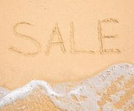 The word Sale written in the sand on beach Stock Image