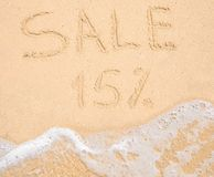 The word Sale 15% written in the sand on beach Stock Photos