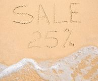 The word Sale 25% written in the sand on beach Stock Image