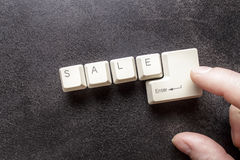 Word sale written using keyboard keys and index finger on the en Royalty Free Stock Images