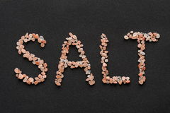 Word Salt written in pink Hymalayan salt crystals. On dark background Stock Image