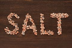 Word Salt written in pink Hymalayan salt crystals. On wooden background Royalty Free Stock Image