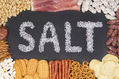 Word salt written with sea salt surrounded by food containing a lot of salt Royalty Free Stock Photos