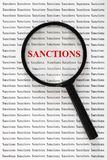 Word sanctions of red letters under loupe. Concept of increasing, expanding or considering sanctions. Word `sanctions` of red letters under loupe. Concept of royalty free stock photos