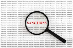 Word sanctions of red letters under loupe. Concept of increasing, expanding or considering sanctions. Word `sanctions` of red letters under loupe. Concept of royalty free stock image