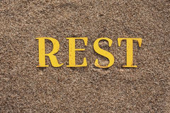 Word on the sand. Laid out word REST on sand Stock Image
