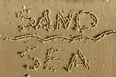 Word of sand, sea written on the sand Royalty Free Stock Photos