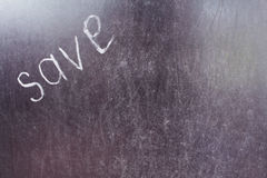 Word save written left with white chalk on a blackboard. Royalty Free Stock Photos