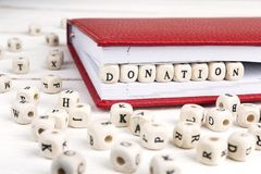 Word Schenking in houten blokken in rood notitieboekje op wit wordt geschreven dat Stock Foto's