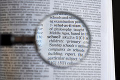 The word school. Magnifying lens over the word school on dictionary Royalty Free Stock Photos