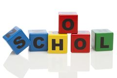 SCHOOL spelled with alphabet building blocks. Word school spelled with wooden alphabet building blocks isolated on white stock photography
