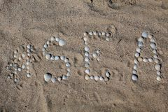 The word sea in English, laid out on the sand with shells. royalty free stock image