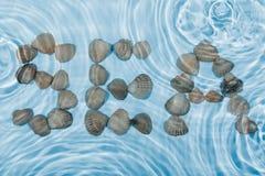 Word sea made ��seashells in water Royalty Free Stock Photos