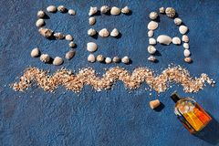 Word sea made of seashells, decorative sea wave, golden sand, colored glass bottle with cork on blue background top view close up stock photos