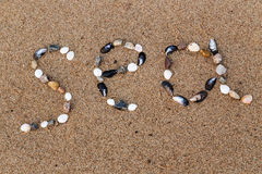 Word sea made of shells and pebbles on the sand Stock Photo