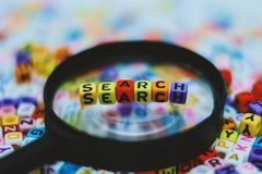 Word `SEARCH` on the magnifying glass. With alphabet letter beads background, Search engine optimization concept added color filter Stock Photo