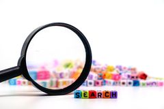 Word `SEARCH` on the magnifying glass with alphabet letter beads background. Search engine optimization concept royalty free stock photography